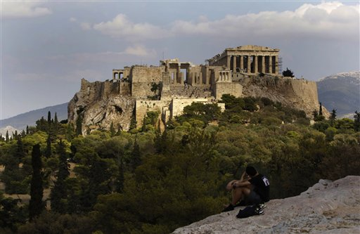 In this photo taken Sunday, Sept. 5, 2010, visitors sit on a rocky outcrop looking out onto the Acropolis, with the newly-restored temple of Athena Nike, distinguished by its four Ionic columns, on a platform below and to the left of the Parthenon, in Athens, Sunday, Sept. 5, 2010. A ten-year restoration project has just been completed on the 2,400-year-old temple, which was dismantled to ground level and rebuilt to correct damage from ground subsidence and rusting internal joints. (AP Photo/Petros Giannakouris)