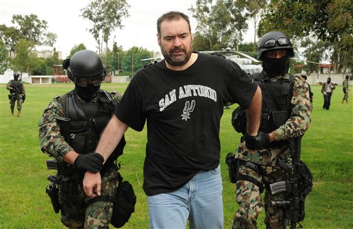 Marines escort alleged drug kingpin Sergio Villarreal Barragan, aka 'El Grande,' center, during his presentation to the press in Mexico City, Monday, Sept. 13, 2010. Villarreal, an alleged leader of the Beltran Leyva drug cartel, was captured in a raid Sunday, according to a statement released by the Mexican Navy. (AP Photo/Miguel Tovar)