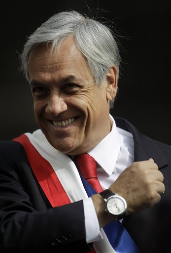 Chile's President Sebastian Pinera gestures from a carriage in route to the Metropolitan Cathedral to attend a TeDeum mass as part of the celebrations of Chile's Independence bicentennial celebrations in Santiago, Chile, Saturday, Sept. 18, 2010. (AP Photo/ Roberto Candia)