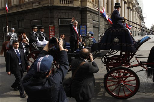 Chile's President Sebastian Pinera, center, waves from a carriage in route to the Metropolitan Cathedral to attend a TeDeum mass as part of Chile's Independence bicentennial celebrations in Santiago, Chile, Saturday, Sept. 18, 2010. (AP Photo/ Roberto Candia)