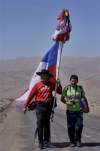 Ruben Naveas, better known as the walking 'Huaso', left, holds a Chilean flag as he walks towards the San Jose mine along the Atacama dessert accompanied by Jose Sanchez, cousin of Pablo and Esteban Rojas, two of the trapped miners at the mine in Copiapo, Chile, Saturday, Sept. 18, 2010. Thirty-three miners have been trapped deep underground in the copper and gold mine since it collapsed on Aug. 5. A 'Huaso' is a Chilean traditional character. (AP Photo/Aliosha Marquez)