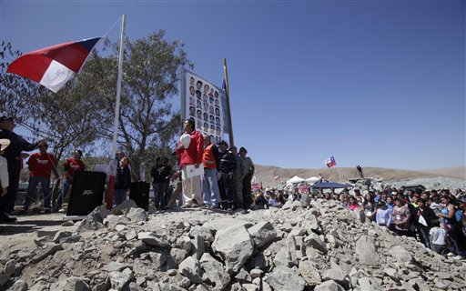 Relatives of 33 trapped miners and authorities sing their national anthem next to a Chilean flag sent by the miners with their names and signatures on it, during Chile's Independence bicentennial celebrations at the San Jose mine in Copiapo, Chile, Saturday, Sept. 18, 2010. The miners have been trapped deep underground in the copper and gold mine since it collapsed on Aug. 5. (AP Photo/Aliosha Marquez)