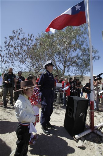 Vicente Valderrama, left, and Paloma Benitez, center, grandchild and niece respectively, of trapped miner Jose Ojeda, sing their national anthem next to a Chilean flag sent by the miners with their names and signatures on it, during Chile's Independence bicentennial celebrations at the San Jose mine in Copiapo, Chile, Saturday, Sept. 18, 2010. Thirty-three miners have been trapped deep underground in the copper and gold mine since it collapsed on Aug. 5. (AP Photo/Aliosha Marquez)