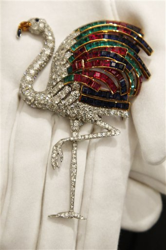 A Sotheby's employee holds a 1940 ruby, sapphire, emerald, citrine and diamond clip on display at the auction house in London, Thursday, Sept. 23, 2010. The clip, formerly in the collection of the Duchess of Windsor, and created by Jeanne Toussaint for Cartier is to be auctioned in 'The Jewels of the Duchess of Windsor' sale on Nov. 30 with an estimated price of 1,000,000 to 1,500,000 pounds (US$1,566,416 to 2,349,624 or euros1,175,595 to 1,763,392). (AP Photo/Sang Tan)