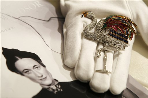 A Sotheby's employee poses with a 1940 ruby, sapphire, emerald, citrine and diamond clip on display at the auction house in London, Thursday, Sept. 23, 2010. The clip, formerly in the collection of the Duchess of Windsor, created by Jeanne Toussaint for Cartier is to be auctioned in 'The Jewels of the Duchess of Windsor' sale on Nov. 30 with an estimated price of 1,000,000 to 1,500,000 pounds (US$1,566,416 to 2,349,624 or euros 1,175,595 to 1,763,392). (AP Photo/Sang Tan)