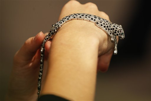 A Sotheby's employee pose with a 1952 onyx and diamond panther bracelet on display at the auction house in London, Thursday, Sept. 23, 2010. The bracelet made by Cartier, formerly in the collection of the Duchess of Windsor is to be auctioned in 'The Jewels of the Duchess of Windsor' sale on Nov. 30 with an estimated price of 1,000,000 to 1,500,000 pounds (US$1,566,416 to 2,349,624 or 1,175,595 to 1,763,392 euro). (AP Photo/Sang Tan)