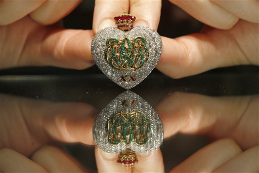A Sotheby's employee pose with a 1957 emerald, ruby and diamond brooch on display at the auction house in London, Thursday, Sept. 23, 2010. The brooch, formerly in the collection of the Duchess of Windsor, is made by Cartier to commemorate the Duke and Duchess twentieth wedding anniversary is to be auctioned in 'The Jewels of the Duchess of Windsor' sale on Nov. 30 with an estimated price of 100,000 to 150,000 pounds (US$156,641 to 234,962 or 117,559 to 176,339 euro). (AP Photo/Sang Tan)