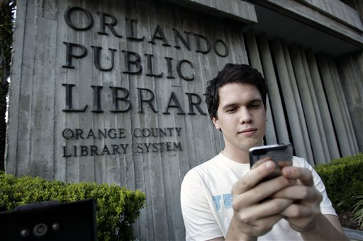 Hillard Goodspeed uses an ipod application called 'shake it', to find reading suggestions at the Orlando Public Library in Orlando, Fla., Wednesday, Sept. 1, 2010.(AP Photo/John Raoux)