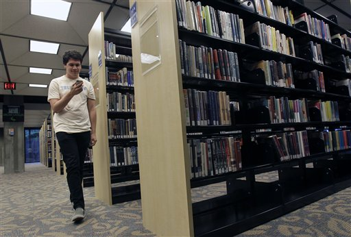 Hillard Goodspeed walks by rows of books as he uses an ipod application called 'shake it', to find reading suggestions at the Orlando Public Library in Orlando, Fla., Wednesday, Sept. 1, 2010.(AP Photo/John Raoux)