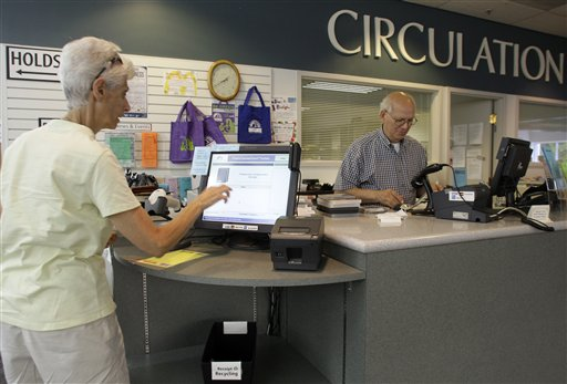 Sandra Snaith, left, of Columbus, uses the self-checkout computer as library employee David Agriesti checks in returned books at the Grandview Heights Public Library Wednesday, Sept. 1, 2010, in Grandview Heights, Ohio. (AP Photo/Jay LaPrete)