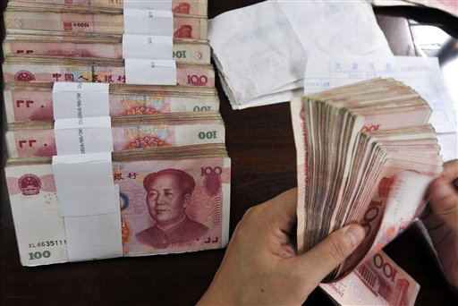 In this Tuesday, Sept. 21, 2010 photo, a cashier counts Chinese currency notes for workers at a office in Rizhao in east China's Shandong province. China on Thursday, Sept. 30, 2010 rejected a measure passed by U.S. lawmakers to allow sanctions over currency manipulation as protectionist and a violation of global free-trading rules. (AP Photo) ** CHINA OUT **