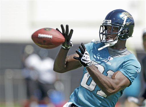 FILE - This June 8, 2010, file photo shows Jacksonville Jaguars wide receiver Kassim Osgood catching a pass during football workouts in Jacksonville, Fla. Osgood leapt out a second-floor window to escape a gun-wielding man who attacked him and a 19-year-old woman. According to the Jacksonville Sheriff's Office, the armed intruder exchanged gunfire with his ex-girlfriend, Mackenzie Rae Putnal, after putting a gun to her head on Monday night, Sept. 27, 2010. (AP Photo/John Raoux, File)