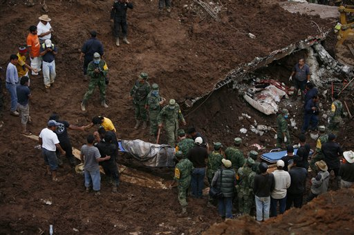 People carry the body of a landslide victim as another body lies in the bed of a home that collapsed in Santa Maria de Tlahuitoltepec in Oaxaca state, Mexico, Wednesday Sept. 29, 2010. A hillside collapsed on the town in the rain-soaked southern state of Oaxaca. (AP Photo/Miguel Tovar)