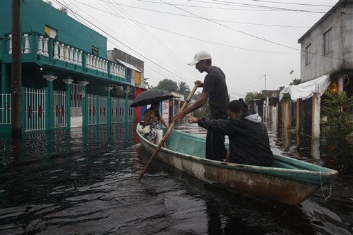 People use a boat to cross a flooded street in the town of Centla in the state of Tabasco, Mexico, Wednesday Sept. 29, 2010. The area has been battered by the remnants of a hurricane and a tropical storm that followed. (AP Photo/America Rocio)