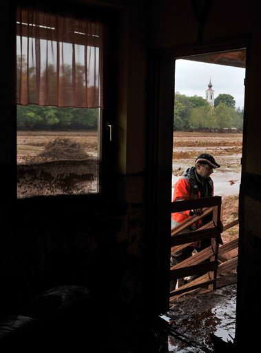 Balazs Holczer returns to his house flooded by toxic mud in Kolontar, Hungary, Wednesday, Oct. 6, 2010. Emergency workers and construction crews on Wednesday swept through the Hungarian towns hardest hit by a flood of toxic sludge, trying to clear roads and homes of acres (hectares) of deep red mud and caustic water. Hundreds of people were evacuated after the disaster Monday, when a gigantic sludge reservoir burst its banks at metals plant in Ajka, a town 100 miles (160 kilometers) southwest of Budapest, the capital. The torrent inundated homes, swept cars off roads and damaged bridges, disgorging an estimated 1 million cubic meters (35.3 million cubic feet) of toxic waste onto several nearby towns. (AP Photo/Bela Szandelszky)