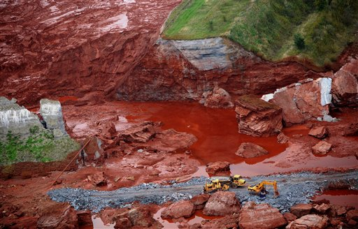 An aerial view of excavators working at a broken dyke of a reservoir that contained red mud of an alumina factory near Ajka, 156 kms southwest of Budapest, Hungary, Wednesday, Oct. 6, 2010. The dyke broke on Monday, and over one million cubic meters of the poisonous chemical sludge inundated three villages, killing a number of people, injuring over a hundred and causing hundreds of families be evacuated. (AP Photo/MTI, Sandor H. Szabo)