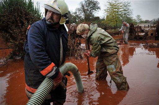 Hungarian fire fighters clean a yard flooded by toxic mud in Devecser, Hungary, Wednesday, Oct. 6, 2010. Monday's flooding was caused by the rupture of a red sludge reservoir at an alumina plant in western Hungary and has affected seven towns near the Ajkai, 100 miles (160 kilometers) southwest of Budapest. The flood of toxic mud killed a yet unknown number of people, injured more than one hundred, with some people still missing. (AP Photo/Bela Szandelszky)