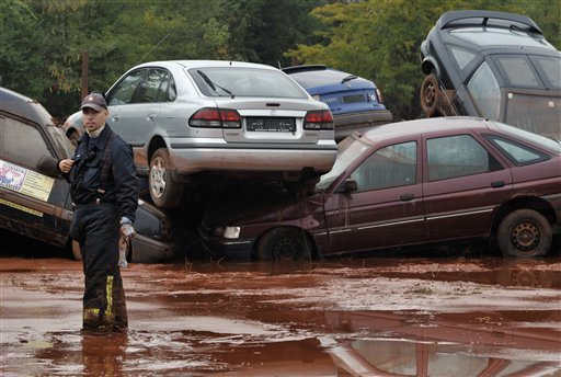 A Hungarian firefighter stands in front of a pile of cars destroyed by flooding toxic mud in Devecser, Hungary, Wednesday, Oct. 6, 2010. Monday's flooding was caused by the rupture of a red sludge reservoir at an alumina plant in western Hungary and has affected seven towns near the Ajkai, 100 miles (160 kilometers) southwest of Budapest. The flood of toxic mud killed a yet unknown number of people, injured more than one hundred, with some people still missing. (AP Photo/Bela Szandelszky)