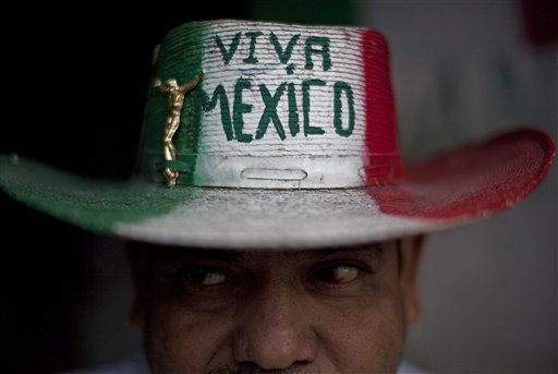 Street vendor Victor Manuel Jimenez, 44, poses for a portrait outside his home as he wears a hat that reads in Spanish 'Long live Mexico' in Tijuana, Mexico, Wednesday Oct. 6, 2010. A two-week $5 million festival called Innovative Tijuana starts Thursday Oct. 7, 2010 in the border city across from San Diego and aims to showcase the city's economic prowess and cultural riches in an effort to demonstrate the city is no longer in the grip of warring drug traffickers. (AP Photo/Guillermo Arias)