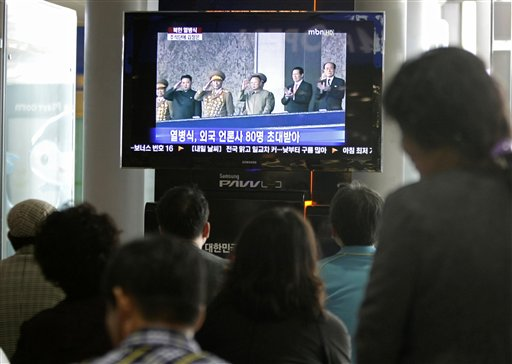 South Koreans watch a TV news program showing North Korean leader Kim Jong Il, third from right in the screen, and his youngest son Kim Jong Un, second from left, at the Seoul Railway Station in Seoul, South Korea, Sunday, Oct. 10, 2010. Clapping, waving and even cracking a smile, Kim Jong Il's son and heir apparent joined his father Sunday at a massive military parade in his most public appearance since being unveiled as North Korea's next leader. (AP Photo/Ahn Young-joon)