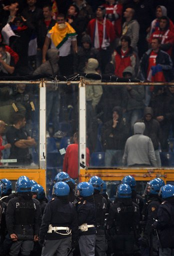 Italian police confront Serbia fans behind a partition prior to the start of a Group C, Euro 2012 qualifying soccer match between Italy and Serbia, at the Luigi Ferraris stadium in Genoa, Italy, Tuesday, Oct. 12, 2010. The Italy-Serbia European Championship qualifier was stopped after seven minutes of play on Tuesday after Serbia fans threw flares onto the pitch. (AP Photo/Antonio Calanni)