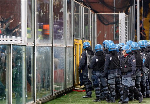 Italian police confront Serbia fans partially seen behind a partition at left prior to the start of a Group C, Euro 2012 qualifying soccer match between Italy and Serbia, at the Luigi Ferraris stadium in Genoa, Italy, Tuesday, Oct. 12, 2010. The Italy-Serbia European Championship qualifier was stopped after seven minutes of play on Tuesday after Serbia fans threw flares onto the pitch. (AP Photo/Antonio Calanni)