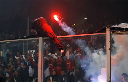 A Serbia fan cuts a net as he climbs onto a partition as a flare is thrown prior to the start of a Group C, Euro 2012 qualifying soccer match between Italy and Serbia, at the Luigi Ferraris stadium in Genoa, Italy, Tuesday, Oct. 12, 2010. The Italy-Serbia European Championship qualifier was called off after seven minutes of play on Tuesday after Serbia fans threw flares and fireworks onto the pitch. (AP Photo/Antonio Calanni)
