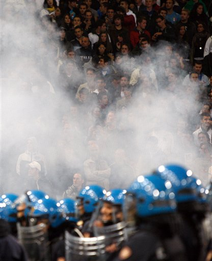 Spectators look on from behind smoke blowing from a flare and Italian police confront Serbia fans, not pictured, prior to the start of a Group C, Euro 2012 qualifying soccer match between Italy and Serbia, at the Luigi Ferraris stadium in Genoa, Italy, Tuesday, Oct. 12, 2010. The Italy-Serbia European Championship qualifier was called off after seven minutes of play on Tuesday after Serbia fans threw flares and fireworks onto the pitch. (AP Photo/Antonio Calanni)