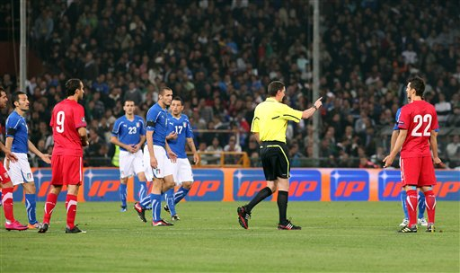 Scottish referee Craig Thomson, center with yellow jersey, talks to Italy and Serbia players while the Group C, Euro 2012 qualifying soccer match between Italy and Serbia is suspended, at the Luigi Ferraris stadium in Genoa, Italy, Tuesday, Oct. 12, 2010. The Italy-Serbia European Championship qualifier was called off after seven minutes of play on Tuesday after Serbia fans threw flares and fireworks onto the pitch. (AP Photo/Carlo Baroncini)