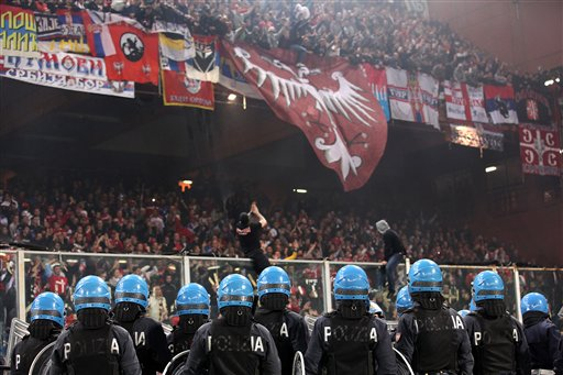 Italian police face Serbia fans prior to the start of a Group C, Euro 2012 qualifying soccer match between Italy and Serbia, at the Luigi Ferraris stadium in Genoa, Italy, Tuesday, Oct. 12, 2010. The start of the Italy-Serbia European Championship qualifier has been delayed due to Serbia fans throwing flares onto the pitch and lighting fireworks. (AP Photo/Carlo Baroncini)