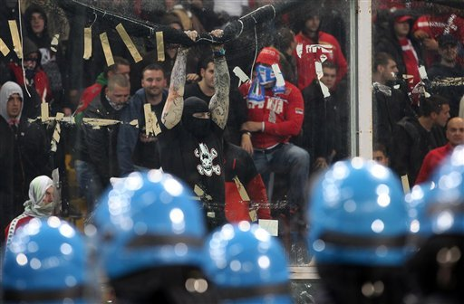 Serbia fans challenge Italian police prior to the start of a Group C, Euro 2012 qualifying soccer match between Italy and Serbia, at the Luigi Ferraris stadium in Genoa, Italy, Tuesday, Oct. 12, 2010. The start of the Italy-Serbia European Championship qualifier has been delayed due to Serbia fans throwing flares onto the pitch and lighting fireworks. (AP Photo/Carlo Baroncini)