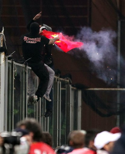 Serbia fan climbs onto a partition and burn what appears to be an Albanian flag prior to the start of a Group C, Euro 2012 qualifying soccer match between Italy and Serbia, at the Luigi Ferraris stadium in Genoa, Italy, Tuesday, Oct. 12, 2010. The Italy-Serbia European Championship qualifier has been stopped after seven minutes of play due to Serbia fans throwing flares onto the pitch and lighting fireworks. (AP Photo/Carlo Baroncini)