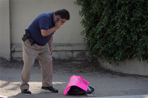 A forensic expert looks at a bag containing a human head with a written message on it outside the newspaper Frontera in Tijuana, Mexico, Tuesday Oct. 12 2010. (AP Photo/Alejandro Cossio)