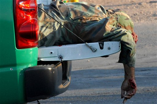 The body of a prison guard lies in the bed of a truck in the northern city of Chihuahua, Mexico, Wednesday, Oct. 13, 2010. Six guards were killed while on their way to pick up a seventh companion a gunmen in another car intercepted them at an intersection and opened fire, according to State Public Safety Department spokesman Fidel Banuelos. (AP Photo/El Diario de Chihuahua)