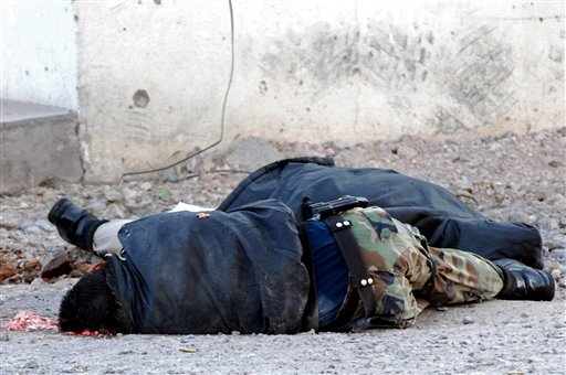 The bodies of two prison guards lie on a road in the northern city of Chihuahua, Mexico, Wednesday, Oct. 13, 2010. Six guards were killed while on their way to pick up a seventh companion, a gunmen in another car intercepted them at an intersection and opened fire, according to State Public Safety Department spokesman Fidel Banuelos. (AP Photo/El Diario de Chihuahua)