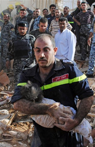 ** CORRECTS GENDER OF CHILD IN SECOND SENTENCE ** An Iraqi emergency worker carries the lifeless body of 6-month-old Shahad Mohammed from the bombed out ruins of his home in Tikrit, 80 miles (130 kilometers) north of Baghdad, Iraq, Tuesday, Oct. 19, 2010. Iraqi officials say a bomb has detonated near the house of a police officer in Saddam Hussein's hometown of Tikrit, killing his 6-month-old niece and several other family members of teh polcie officer. Police and hospital officials say the officer, Lt. Col. Qais Rashid, was unharmed in Tuesday's blast, but his brother, sister and sister-in-law were killed along with his baby niece Shahad Mohammed, Col. Khalid Jassim of Tikrit police said.(AP Photo/Bassim Daham)