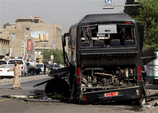 A man passes by a destroyed bus in Baghdad, Iraq, Tuesday, Oct. 19. 2010. Two bombs attached to buses carrying Iranian pilgrims detonated while they drove through downtown, police said. (AP Photo/Hadi Mizban)