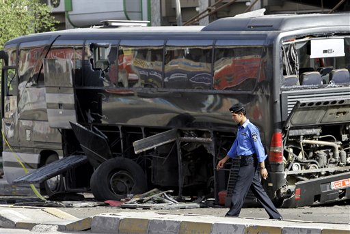 An Iraqi policeman passes by a destroyed bus in Baghdad, Iraq, Tuesday, Oct. 19. 2010. Two bombs attached to buses carrying Iranian pilgrims detonated while they drove through downtown, police said. (AP Photo/Hadi Mizban)
