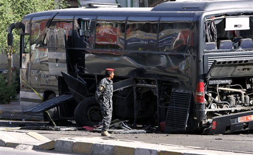 An Iraqi policeman inspects a destroyed bus in Baghdad, Iraq, Tuesday, Oct. 19. 2010. Two bombs attached to buses carrying Iranian pilgrims detonated while they drove through downtown, police said. (AP Photo/Hadi Mizban)