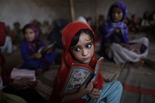 Afghan refugee Aisha Daoud, 4, holds a copy of the Quran while taking part in a daily class to learn how to read verses of the Quran, at a mosque in a poor neighborhood of Rawalpindi, Pakistan, Tuesday, Oct. 19, 2010. (AP Photo/Muhammed Muheisen)