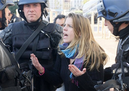 A woman argues with police forces in Lyon, central France, Thursday Oct. 21, 2010. Youths overturned a car and hurled bottles at police in the French city of Lyon amid nationwide tensions over raising the retirement age. Police are chasing the protesters and trying to subdue the violence with tear gas. (AP Photo/Michel Spingler)