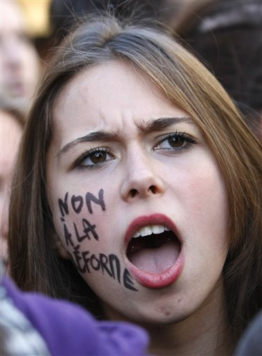 A student shouts slogans during a demonstration in Paris, Thursday Oct.21, 2010. Protesters blockaded Marseille's airport, Lady Gaga canceled concerts in Paris and rioting youths attacked police in Lyon on ahead of a tense Senate vote on raising the retirement age to 62. A quarter of the nation's gas stations were out of fuel despite President Nicolas Sarkozy's orders to force open depots barricaded by striking workers. On her cheek reads: No to the reform. (AP Photo/Francois Mori)