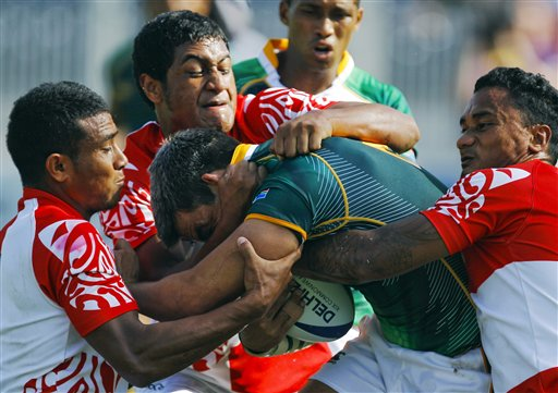 FILE - In this Oct. 11, 2010, file photo, Tonga players try to stop South Africa's Johannes Powell, center, during their rugby sevens match at the Commonwealth Games at Delhi University in New Delhi, India. Though injury rates in rugby are as high or higher than those in American football, there has never been a push to bring helmets and heavy padding into the game. (AP Photo/Victor R. Caivano, File)