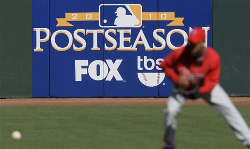 FILE - In this Oct. 18, 2010 file photo, a Philadelphia Phillies player practices in front of an advertisement for postseason baseball on Fox in San Francisco. Fox and Cablevision reached an agreement Saturday that will restore programming to more than 3 million New York-area subscribers who have been without some of their favorite shows and baseball playoff games for two weeks. (AP Photo/Jeff Chiu, File)