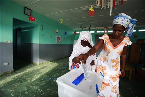 Awa Sylla, right, helps her grandmother Njama Sylla cast her vote for president at a polling station in a nursery school, in the former rebel stronghold of Bouake, in northern Ivory Coast, Sunday, Oct. 31, 2010. The West African nation of Ivory Coast held a long-awaited presidential election Sunday, the first since civil war erupted in 2002 and split the world's leading cocoa producer in half. (AP Photo/Rebecca Blackwell)