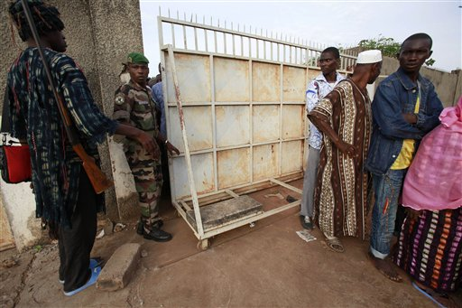 A traditional hunter, left, and a former member of the rebel New Forces army, second left, now part of the national army, control access to a polling station as part of a mixed election security force, in the former rebel stronghold of Bouake, in northern Ivory Coast, Sunday, Oct. 31, 2010. The West African nation of Ivory Coast held a long-awaited presidential election Sunday, the first since civil war erupted in 2002 and split the world's leading cocoa producer in half. (AP Photo/Rebecca Blackwell)