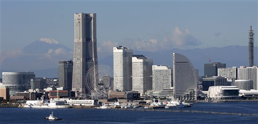 In this Nov. 3, 2010 photo, with a backdrop of snow-capped Mount Fuji, left, Japan's highest mountain, skyscrapers soar at Yokohama port, south of Tokyo. Japan, which hosts the annual Asia-Pacific Economic Cooperation forum next weekend in Yokohama, is embroiled in a flare-up of territorial disputes with China and Russia that is stirring up rancor in all three countries and is already prompting economic fallout. (AP Photo/Itsuo Inouye)