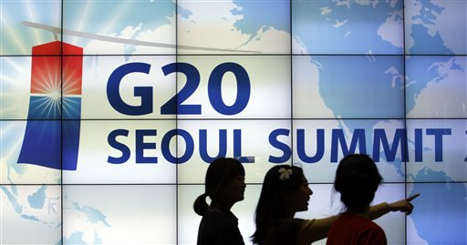 FILE - In this Nov. 2, 2010 file photo, women walk by a screen showing G20 Seoul Summit sign at the venue for the upcoming summit meeting, scheduled on Nov. 11-12 in Seoul, South Korea. World leaders head to back-to-back economic summits in Asia next week, but regional political tensions _ some spawned by China's growing assertiveness _ could undermine attempts to project unity amid a faltering global economic recovery. (AP Phoro/Lee Jin-man, File)