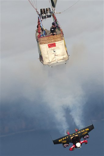 Swiss pilot Yves Rossy, the first man in the world to fly under a jet-fitted wing, speeds through the air to perform a looping near a hot air balloon in Bercher, western Switzerland, Friday, Nov. 5, 2010. (AP Photo/Keystone, pool, Laurent Gillieron)