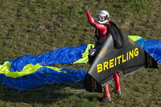 Swiss pilot Yves Rossy, the first man in the world to fly under a jet-fitted wing, celebrates after performing a looping in Denezy, western Switzerland, Friday, Nov 5, 2010. Rossy has completed two aerial loops using his custom-made jet-propelled wingsuit. He jumped from a hot-air balloon above Lake Geneva and performed the daredevil stunt before landing safely with a parachute. (AP Photo/Keystone, Laurent Gillieron, pool photo)